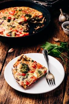 Овощная фриттата с брокколи, красным болгарским перцем и красным луком на белой тарелке и в чугуне