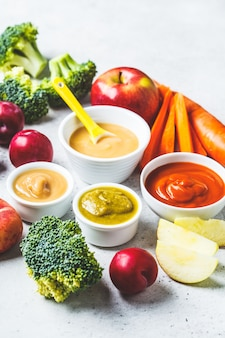 Vegetable and fruit baby puree in white bowls with ingredients.