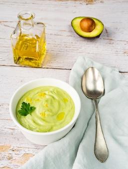 Овощной зеленый крем-суп из огурцов и авокадо с цедрой лимона на светлом фоне. вид сбоку. вертикальная ориентация.
