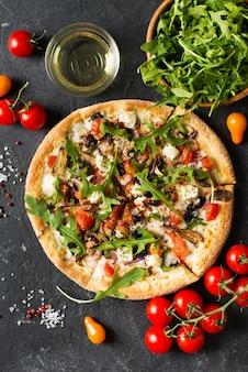 黒の背景、コピースペース、上面図、垂直にトマトと野菜のイタリアンピザ