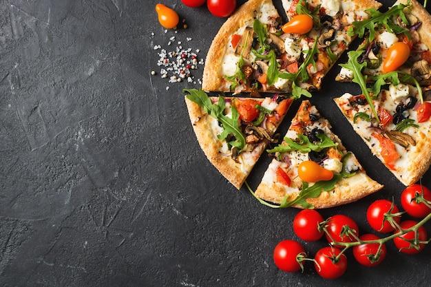 黒の背景、コピースペース、上面図にトマトと野菜のイタリアンピザ