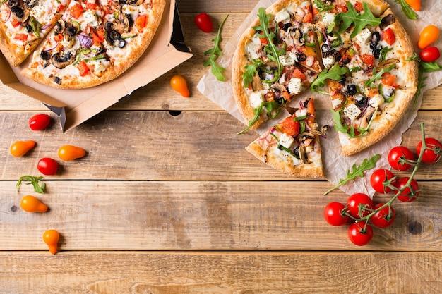 Wodeen背景、コピースペース、上面図にトマトと野菜のイタリアンピザ