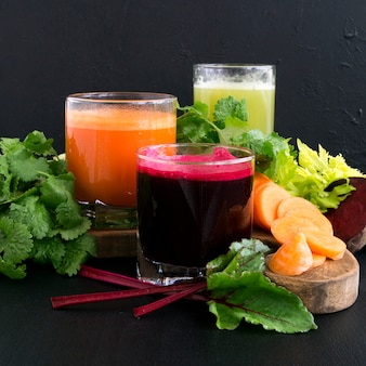 Vegetable juice in glass cups on a black background. beets, celery, carrots.