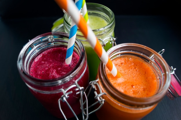 Vegetable juices in jars with tubes on a black background. beet, celery, carrot
