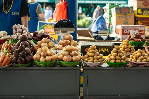 Овощной рынок. продается много разных овощей в разноцветных корзинах рядом друг с другом.