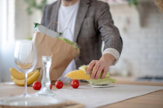野菜メニュー。キッチンでとうもろこし料理を作っている男性