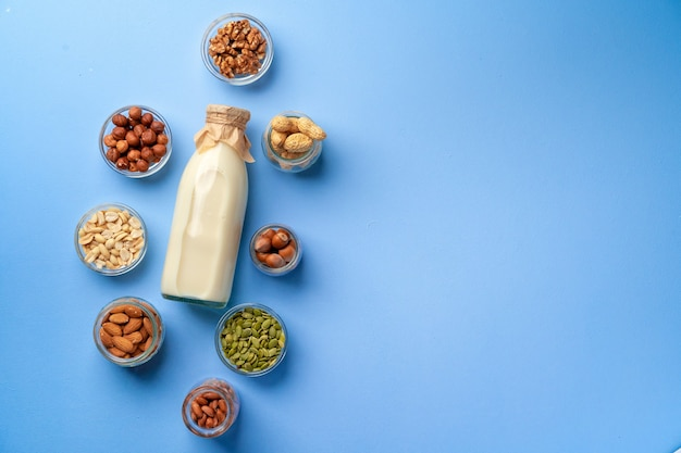 Vegetable milk concept with milk bottle and bowls with grains on blue, top view