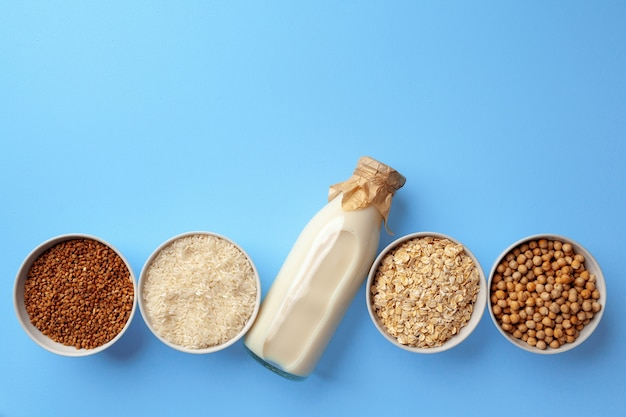 Vegetable milk concept with milk bottle and bowls with grains and nuts on blue background top view