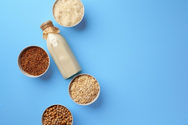 Vegetable milk concept with milk bottle and bowls with grains and nuts on blue