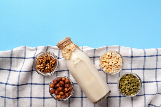 Vegetable milk concept with milk bottle and bowls with grains top view