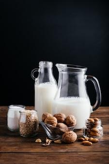 木の背景に野菜ミルク、アーモンドミルク、クルミミルク、ライスミルク、ココナッツミルク