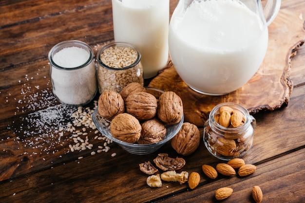 Vegetable milk on wood background almond milk walnut milk rice milk and coconut milk
