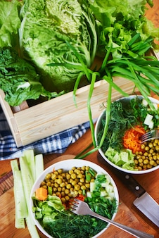 Vegetable mix in bowls with green peas, cucumbers, carrots, lettuce and dill