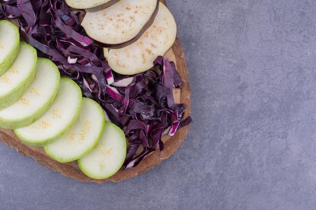 Mix di verdure isolate in un piatto di legno