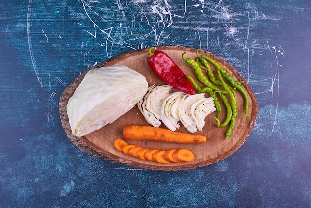 Preparato di verdure su un piatto di legno su uno spazio blu al centro.