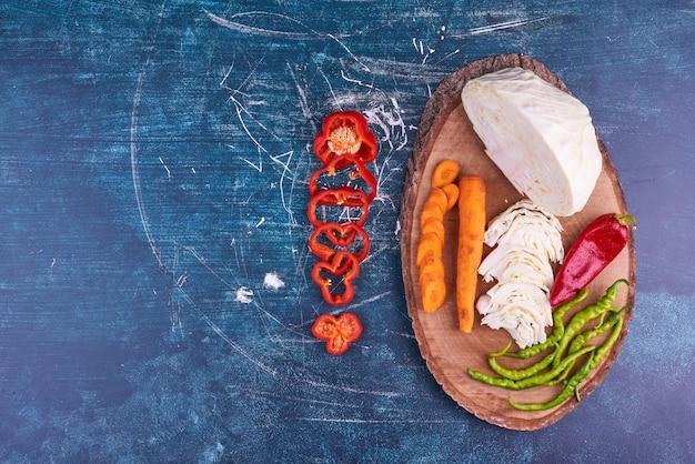 Mix di verdure su un piatto di legno su uno spazio blu.