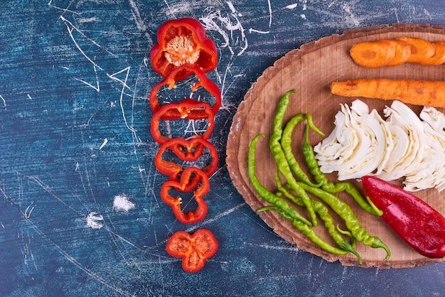 Mix di verdure su un piatto di legno, vista dall'alto.