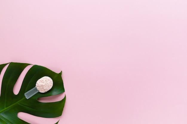 Натуральный гидролизованный растительный порошок коллагена на зеленом листе на розовом. активная пищевая добавка.