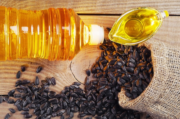 Растительное масло и семена подсолнечника в лачуге на деревянном столе. вид сверху