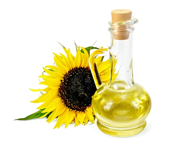 Vegetable oil in a glass carafe with a sunflower isolated on a white background