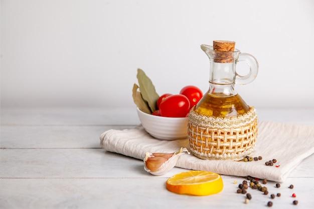 토마토, 레몬, 후추, 베이 리프와 복사 공간이 있는 수건에 병에 든 식물성 기름.