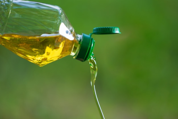 Vegetable oil pouring from bottle with nature background