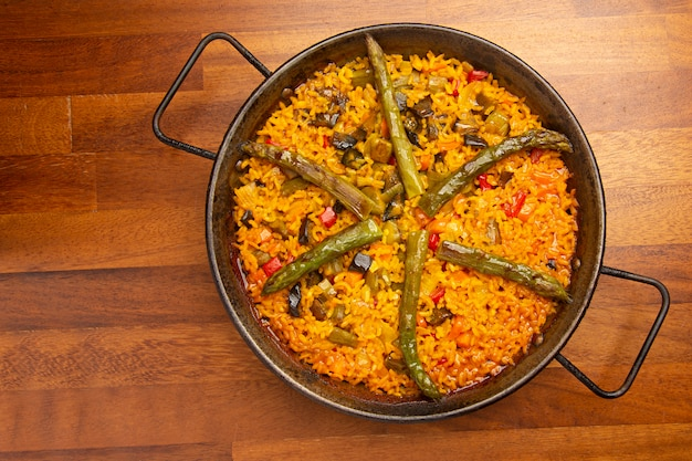 Vegetable paella rice with vegetables in paella pan, on wood.