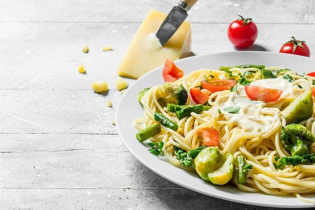 白い素朴なテーブルの上にブロッコリー、トマト、インゲン、パルメザンチーズと野菜のペースト