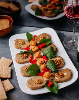 Овощной паштет, сформированный вместе с зелеными листьями внутри белой тарелки вместе с чипсами из красного вина на сером