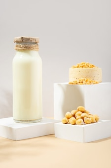 Vegetable pea milk in a bottle and chickpeas in handmade ceramic bowl on white podium, pedestal on beige background. shadows. gluten-free, lactose-free vegan product. modern composition. copy space
