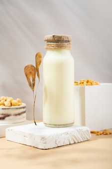 병에 든 야채 완두콩 우유와 흰색 연단에 있는 수제 세라믹 그릇에 있는 병아리 완두콩, 베이지색 배경의 받침대. 그림자. 마른 잎. 글루텐 프리, 락토스 프리 비건 제품. 현대의. 복사 공간