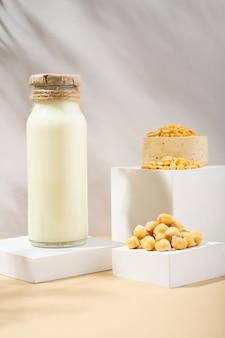 병에 든 야채 완두콩 우유와 흰색 연단에 있는 수제 세라믹 그릇에 있는 병아리 완두콩, 베이지색 배경의 받침대. 그림자. 글루텐 프리, 락토스 프리 비건 제품. 현대 구성입니다. 복사 공간