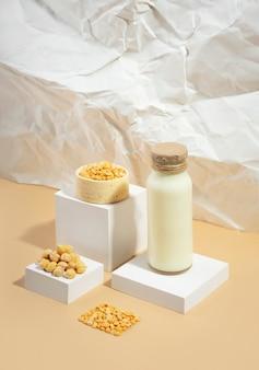 병에 야채 완두콩 우유와 흰색 연단에 그릇에 병아리콩, 베이지색 구겨진 종이 배경에 받침대. 그림자. 유당이 없는 완전채식 제품입니다.현대적인 구성입니다.등각투영 대각선 투영