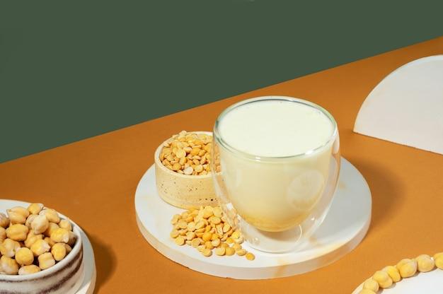 병에 든 야채 완두콩 우유와 흰색 연단에 있는 그릇에 있는 병아리콩, 베이지색 녹색 배경에 받침대. shadows.글루텐과 유당이 없는 비건 채식 제품입니다.현대 구성입니다.등각 투영 투영법