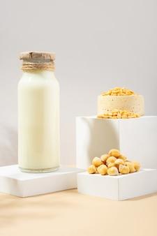 병에 든 야채 완두콩 우유와 흰색 연단에 있는 수제 세라믹 그릇에 있는 병아리콩, 베이지색 배경의 받침대. 그림자. 글루텐 프리, 락토스 프리 비건 제품. 현대 구성입니다. 복사 공간