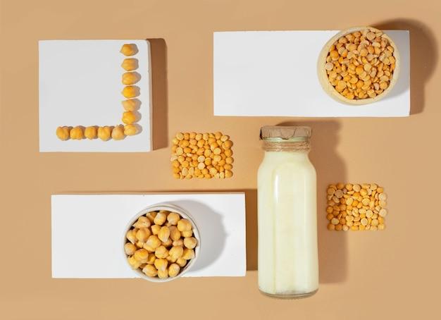 병에 야채 완두콩 우유와 흰색 연단에 병아리콩, 베이지색 배경에 받침대. 그림자. 글루텐 프리, 락토스 프리 비건 제품. 현대적인 평면 구성. 평면도. 확대.
