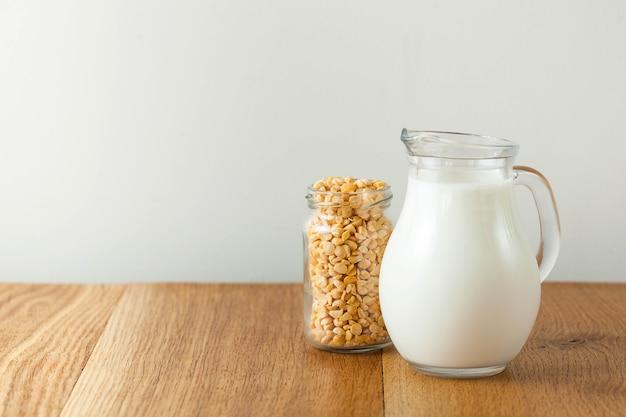 Vegetable pea milk in a milk jug and peas in a jar.