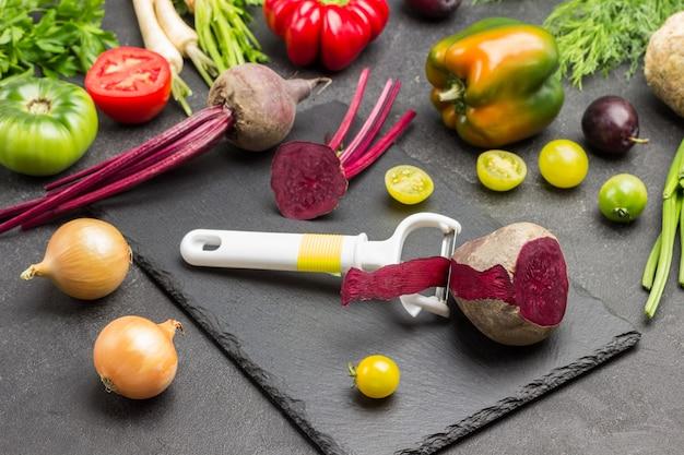まな板の上の野菜の皮むき器とビート。テーブルの上のトマト、ピーマン、緑。黒の背景。上面図