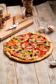 木製のテーブルにオリーブとコショウと野菜のピザ