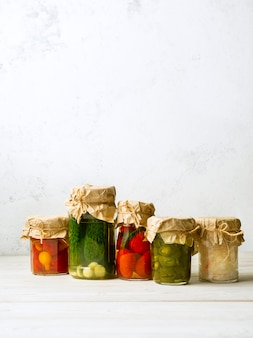 Vegetable preserves in glass jars on white background. vertical image with copy space