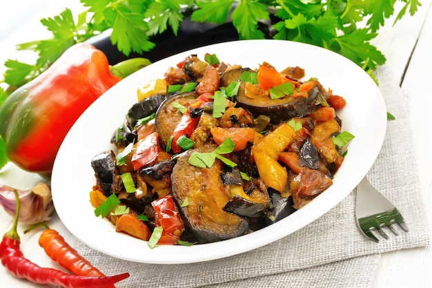 Vegetable ragout with eggplant, tomatoes, sweet and hot peppers, onions, carrots, fried with herbs and spices in plate on a napkin, garlic, parsley on the background of light wooden board