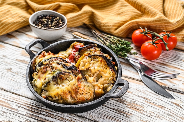 Vegetable ratatouille baked in cast-iron dish. wooden background. top view.