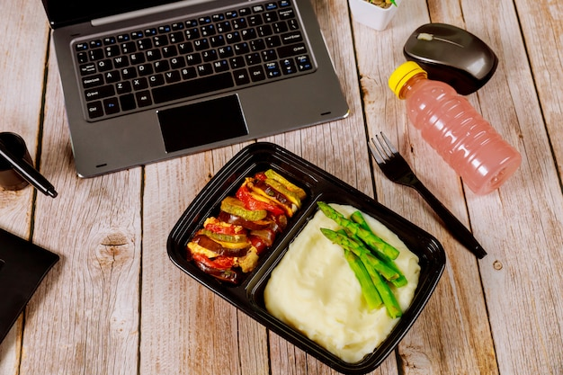 Vegetable ratatouille with mashed potato and asparagus in container for office lunch.