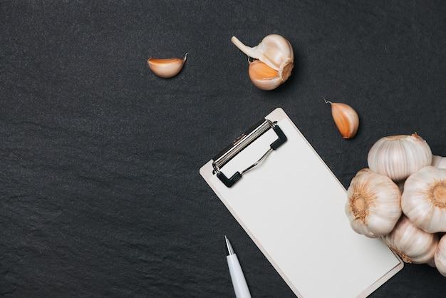 Овощной рецепт. открыть книгу меню с чесноком на темном фоне