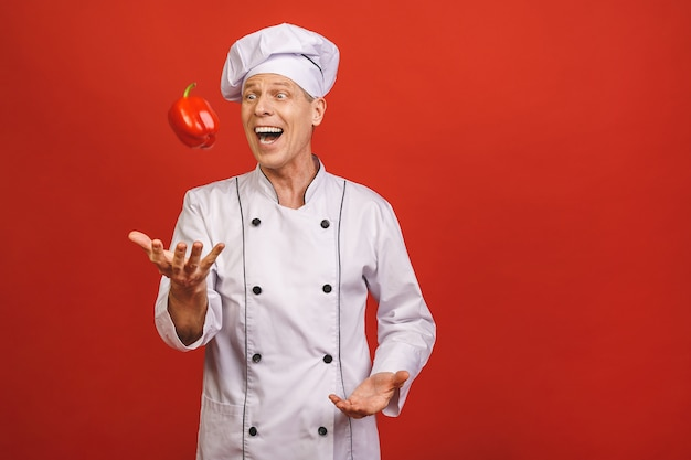 Vegetable recipes. excited senior chef man juggling throwing sweet pepper standing in studio over red background.