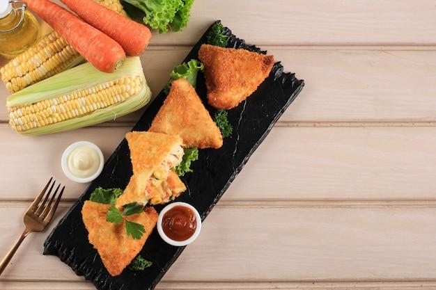 三角形の形をした野菜のリッソール。とうもろこし、にんじん、さやいんげんを詰めた薄いクレープを、チーズ、マヨネーズ、チリソースを添えたブラックストーンプレートでお召し上がりいただけます。木の背景にスペースをコピー