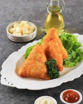 三角形の形をした野菜のリッソール。とうもろこし、にんじん、さやいんげんを詰めた薄いクレープを、チーズ、マヨネーズ、チリソースを添えて白いプレートに盛り付けました。灰色の背景にスペースをコピー