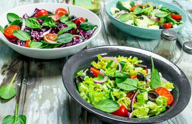 野菜サラダ。素朴なテーブルにさまざまなオーガニックサラダ、オリーブオイルを添えた野菜、スパイス。