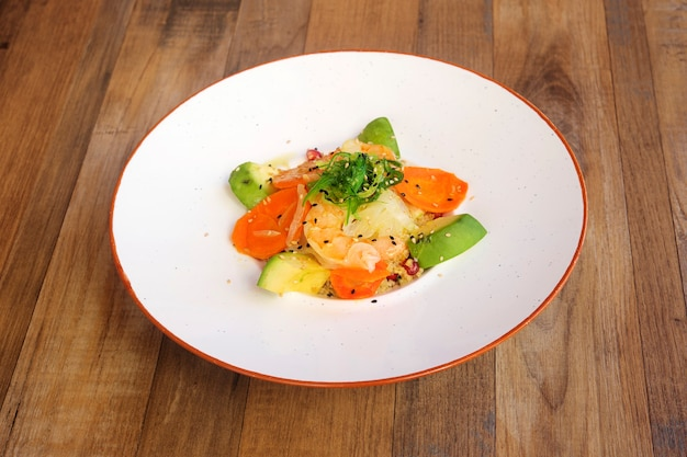 Овощной салат и рыба на деревянных фоне.