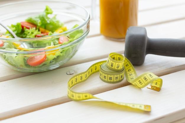 야채 샐러드와 과일 스무디와 아령은 흰색 창턱에 놓여 있습니다. 건강한 라이프 스타일 신체 활동과 적절한 영양의 개념.